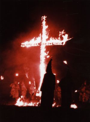 Cross burning with hooded Klansman in front